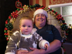 Sitting comfortably - Young Zebediah Lock tries out Santa's chair with Joanne Bateman from Quayside Emporium